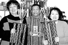 Hilda, Basil and Margaret Simmons holding some of their many trophies